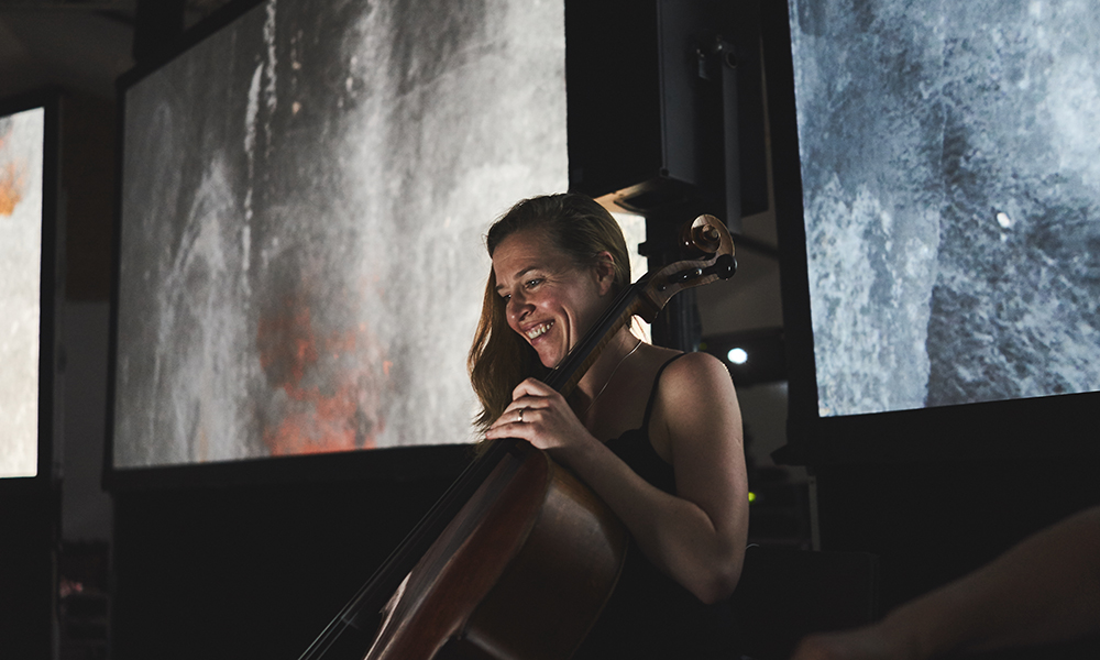 MICROSITE_Naomi laughing playing cello.jpg