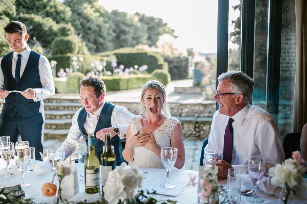 natural photo of bride laughing during the best man speech at the wedding breakfast at chaucer barns
