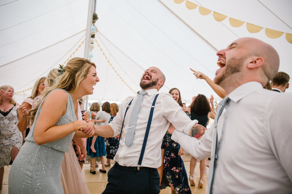 wedding guests laugh uncontrollably on the dance floor of the festival marquee wedding at wildwood bluebell in the cotswolds