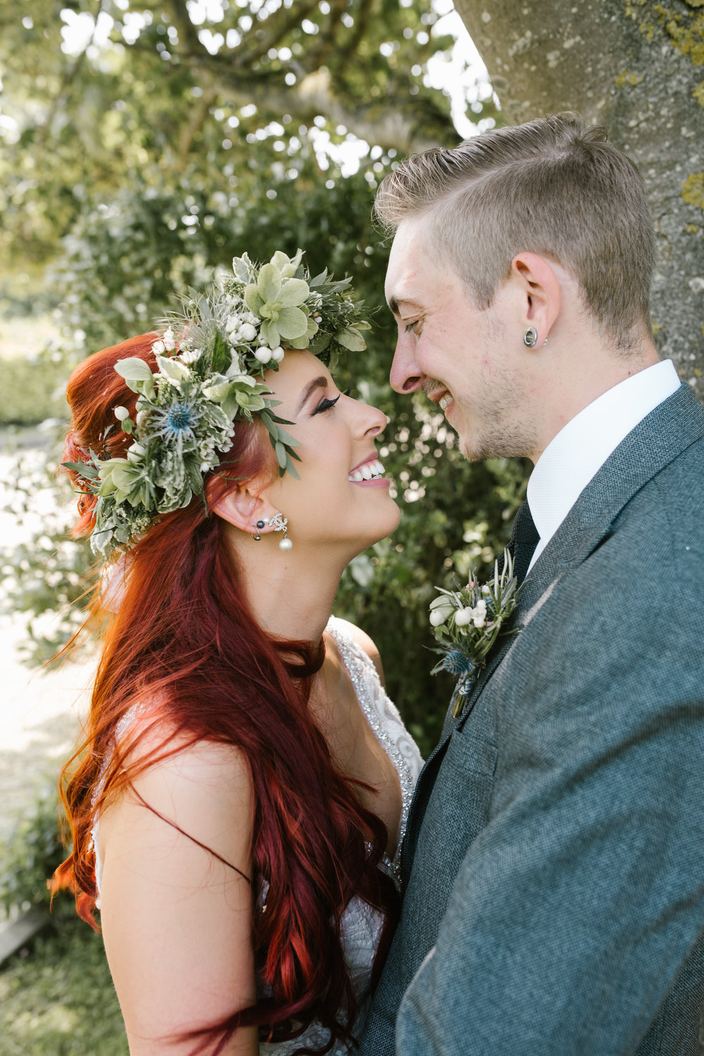 newlyweds smiling at one another, bride is wearing the most amazing flower crown