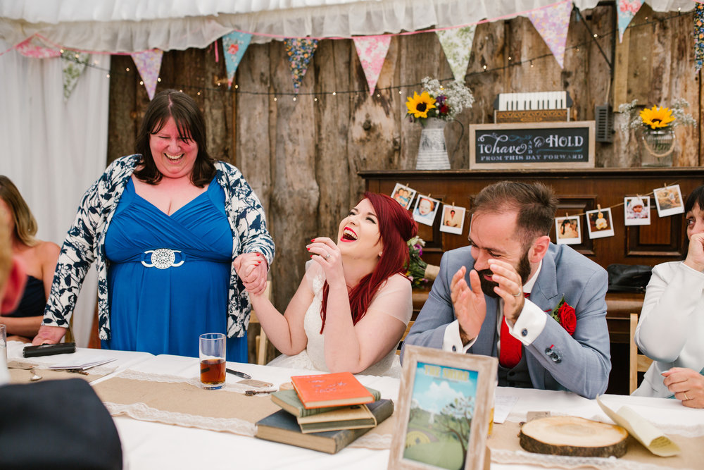 the mother of the bride as she delivers her hilarious speech, and the bride and groom laugh and clap her along, at kingsacre cupcakes in chester- chester wedding photographer
