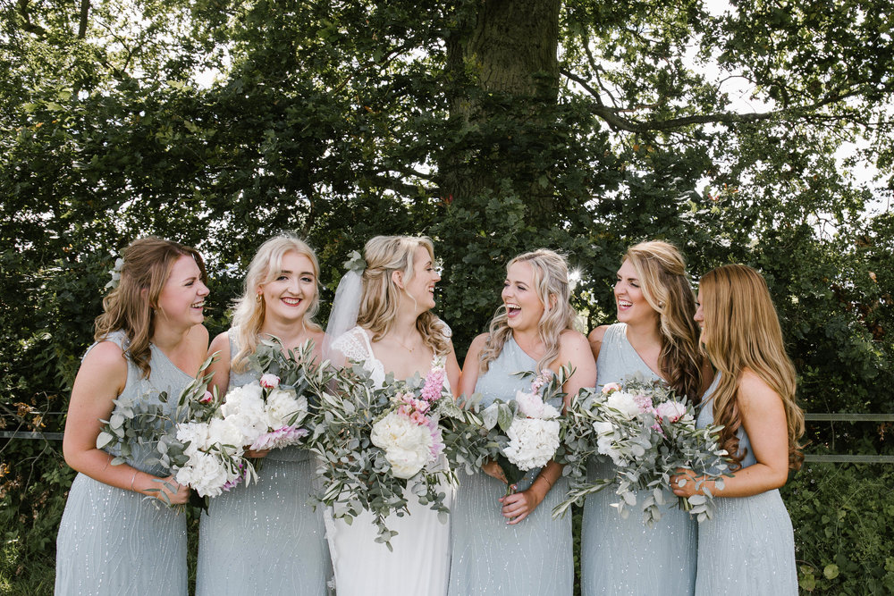 Natural picture of bridesmaids laughing together after the outdoor wedding ceremony at woodland bluebell in the cotswolds