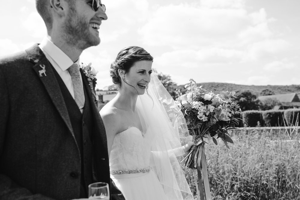 black and white photo at upwaltham barns of bride and groom laughing, and holding hands as they walk through a field