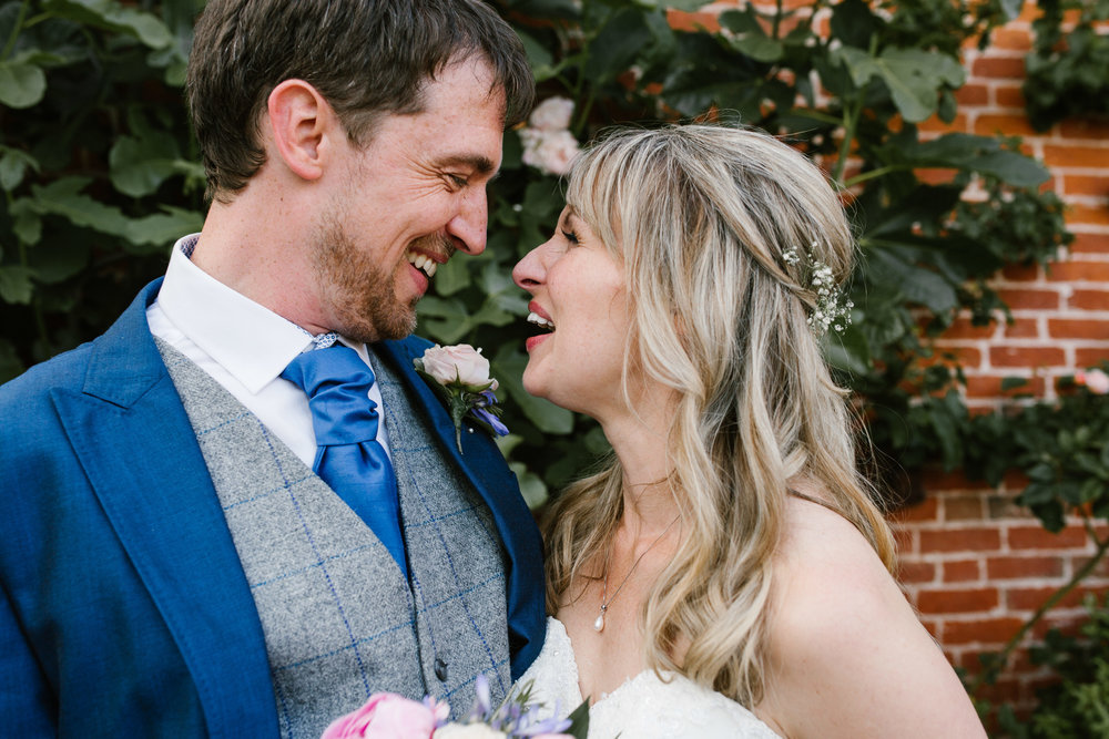 close up of bride and groom laughing in each others face after their summer ceremony at the walled garden at beeston fields