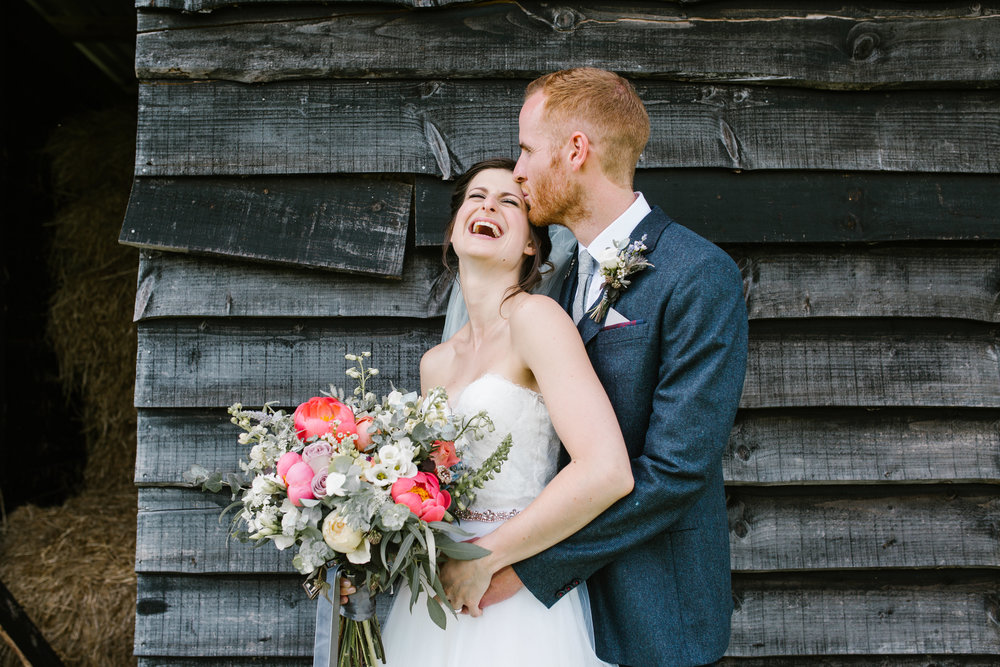 groom kisses his brides head as she laughs hysterically, standing in front of a rustic shed at upwaltham barns- west sussex