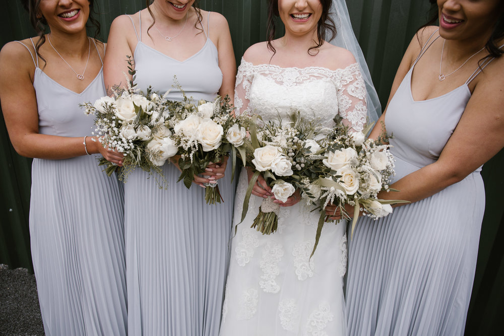 close up photo of bridal party and their beautiful flowers