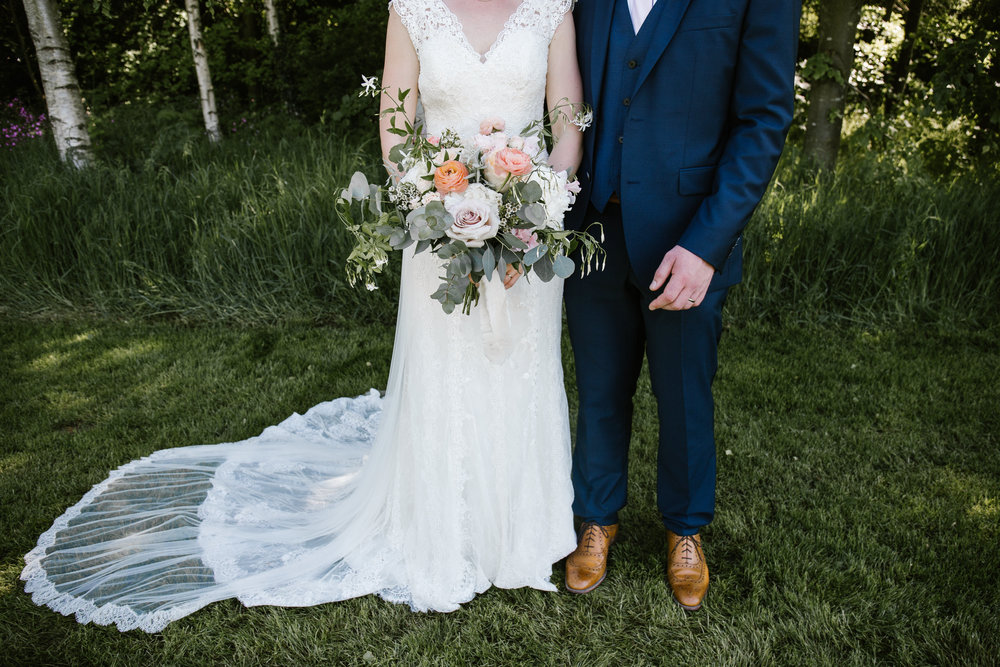 detail photo ofa brides wedding dress, amazing flowers and grooms navy suit and brown shoes, as they stand in the gardens of chaucer barns