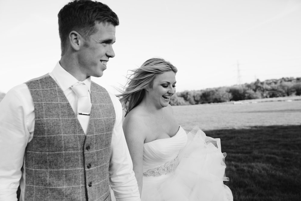 black and white close up photo of a happy bride and groom as they walk hand in hand through a field in staffordshire with the wind blowing in their hair