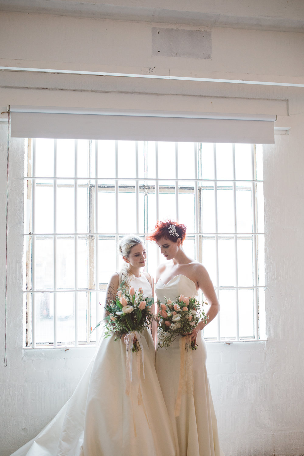 two brides stand in a window at camp and furnace liverpool, looking at one another holding stunning flower bouquets