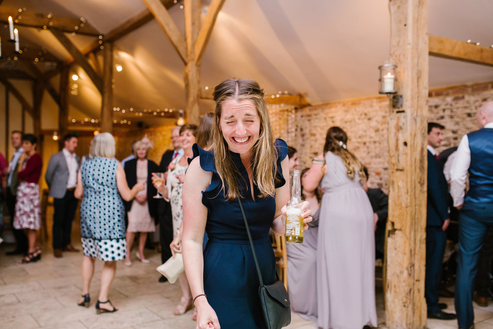 drunk guest smiling at the camera with beer in hand on the dance floor at upwaltham barns