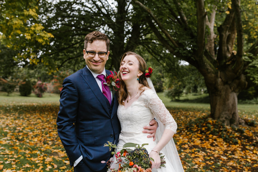 bride and groom laughing together after their autumn wedding ceremony at cowley manor surrounded by fallen leaves