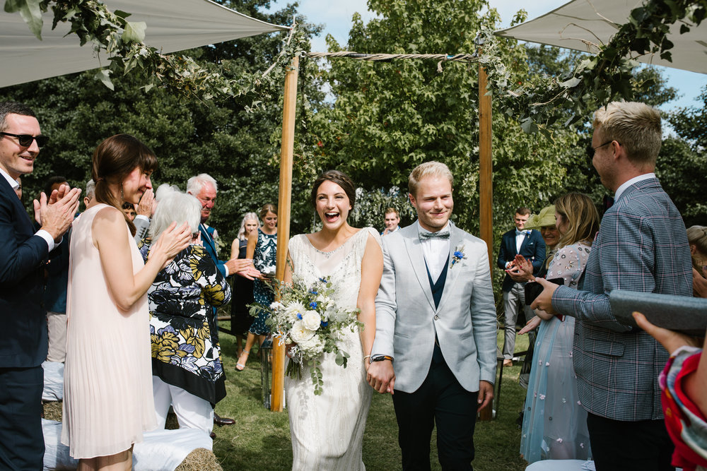 bride and groom walk down the aisle holding hands and cheering after their outdoor back garden wedding ceremony