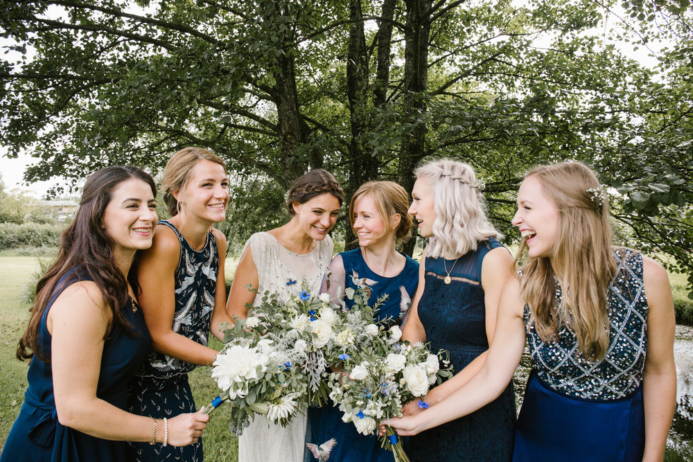 natural photo of bridesmaids laughing together, all wearing navy blue odd bridesmaids dresses