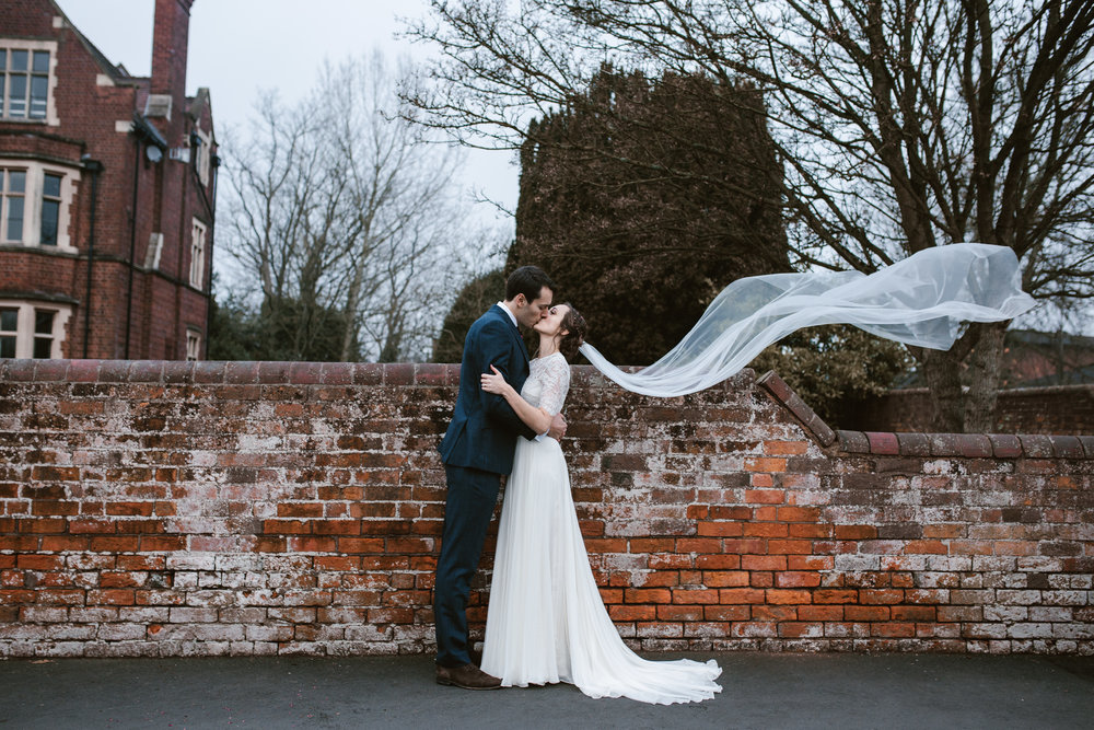 a kissing bride and groom hold onto one another as the brides long veil floats in the air after their winter wedding in birmingham