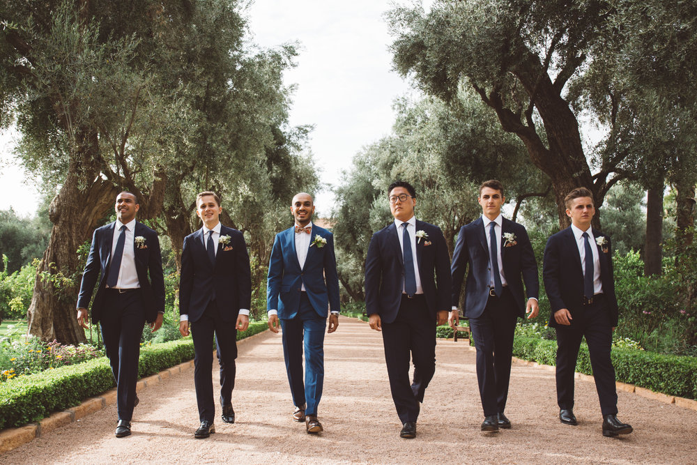 groomsmen all walk in a line towards the outdoor wedding ceremony at la mamounia hotel in marrakech morocco