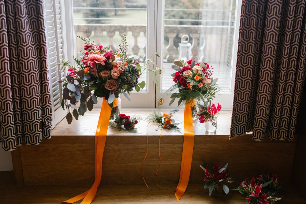 autumnal wedding bouquets as they sit in vases in the window before the wedding ceremony at cowley manor in the cotswolds