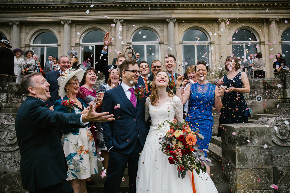 wedding guests crowd around the bride and groom and throw lots of confetti at their autumn wedding at cowley manor in the cotswolds