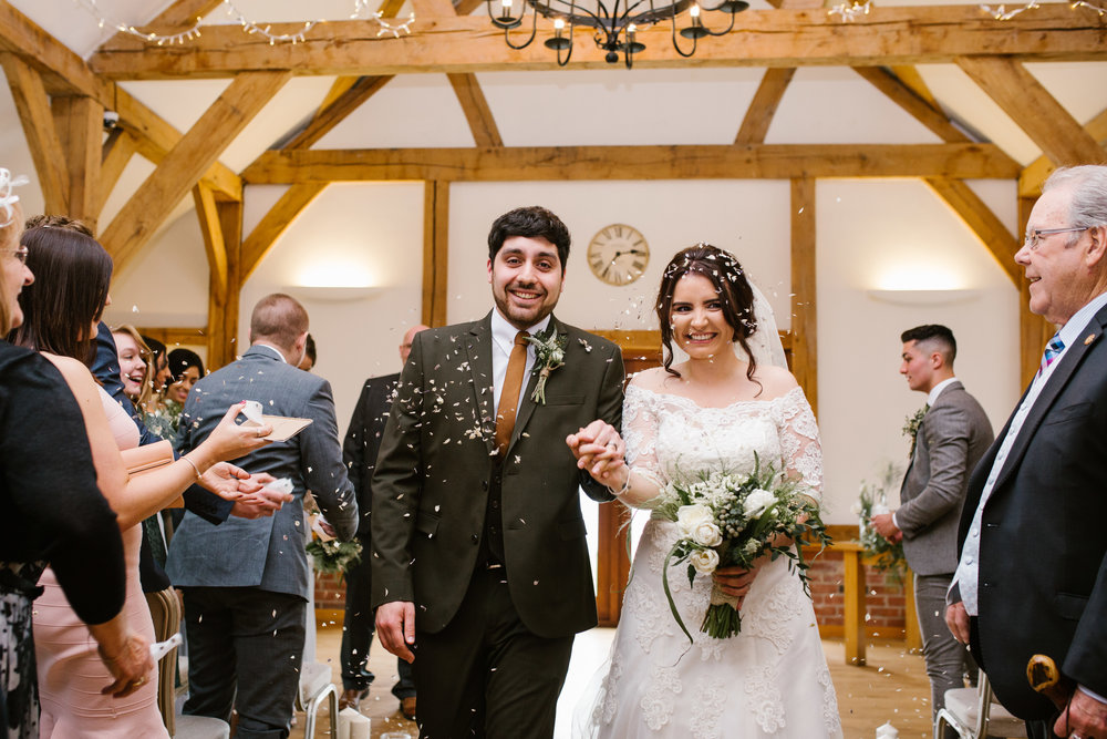bride and groom walking down the aisle, having confetti thrown at them after their sandhole oak barn wedding ceremony- chester wedding photography