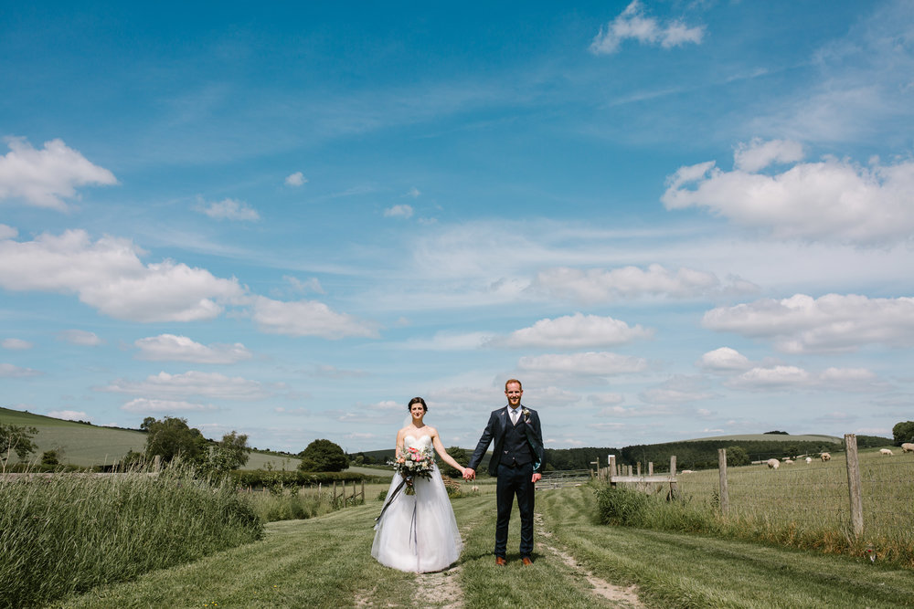 bride and groom stand holding hands in the summer sun, with bright blue skies at their upwaltham barns wedding