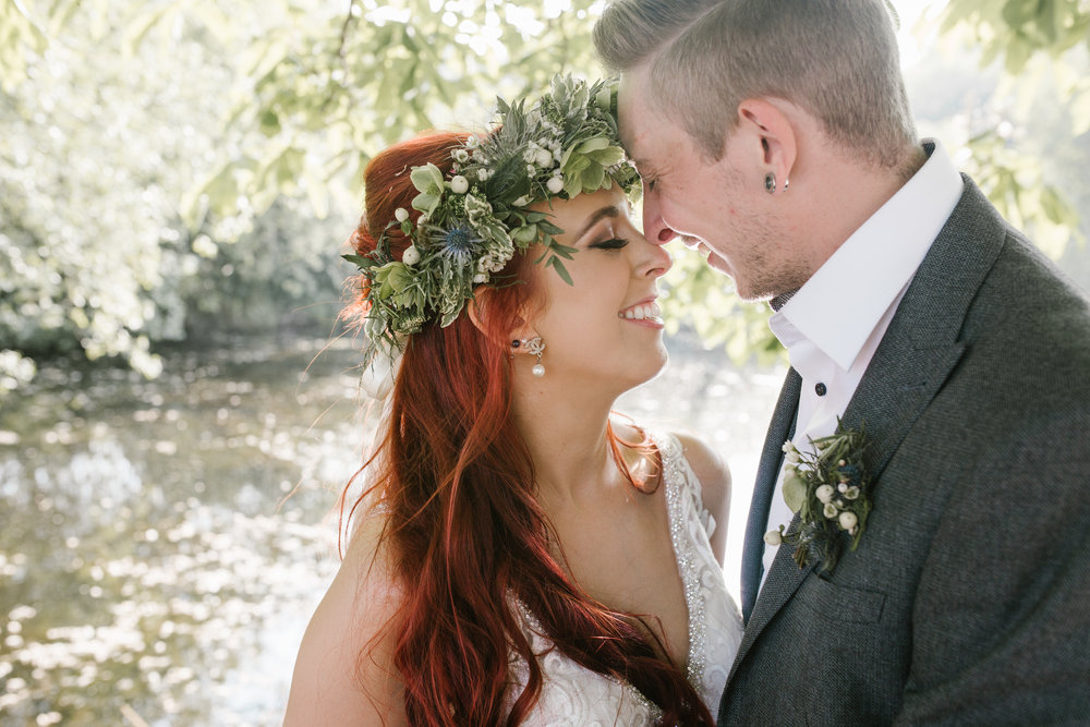 fun and laid back bride and groom smiling happily together at the red barn lingfield