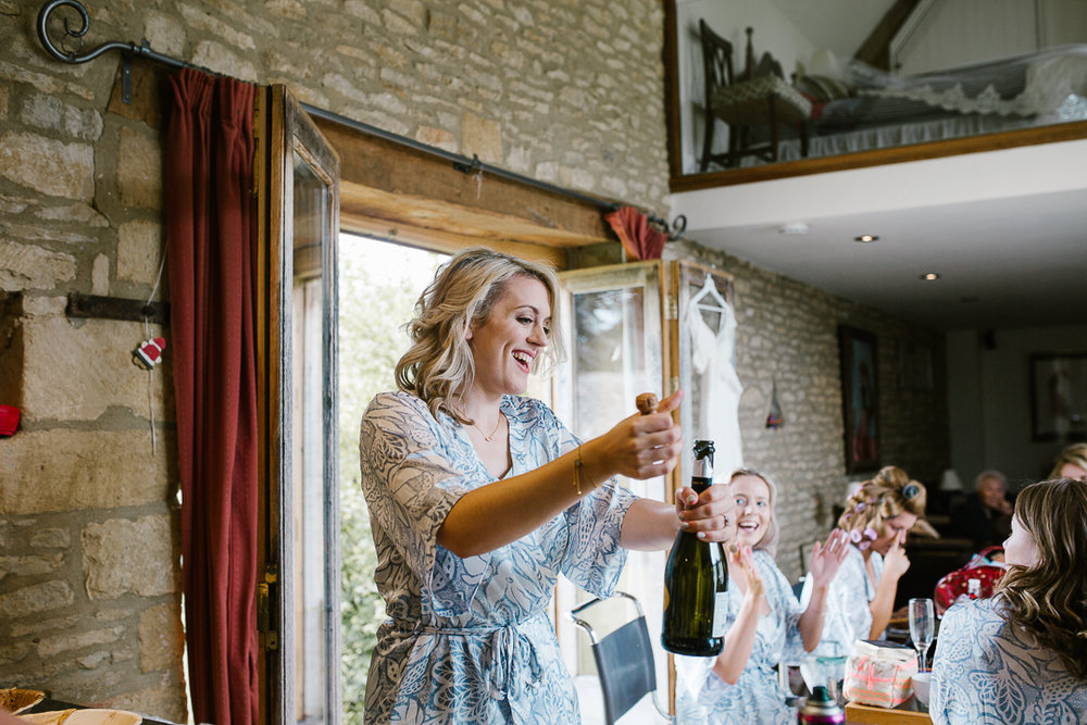 bride popping open the champagne on the morning of her wedding
