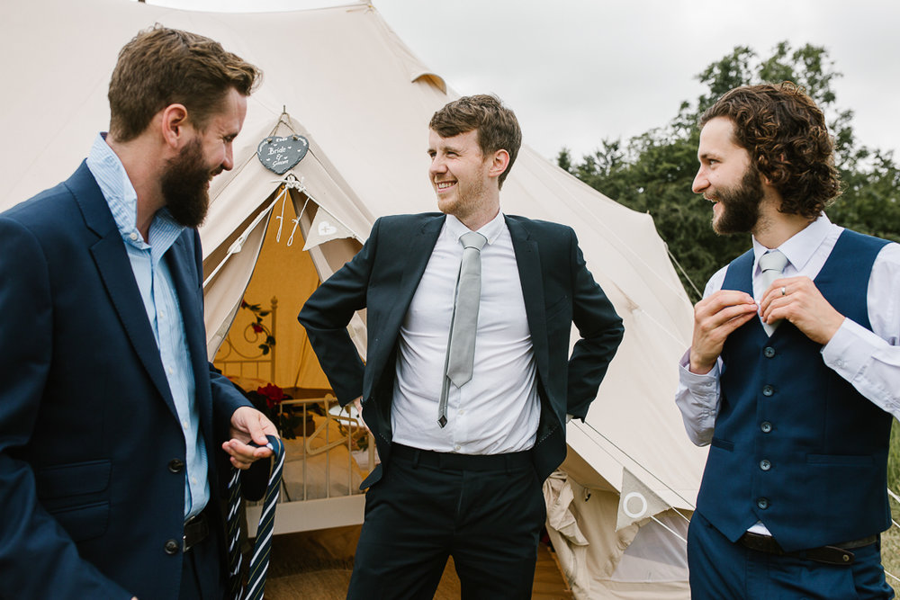 groomsmen tying their ties as they get ready for the outdoor wedding after an evening of glamping