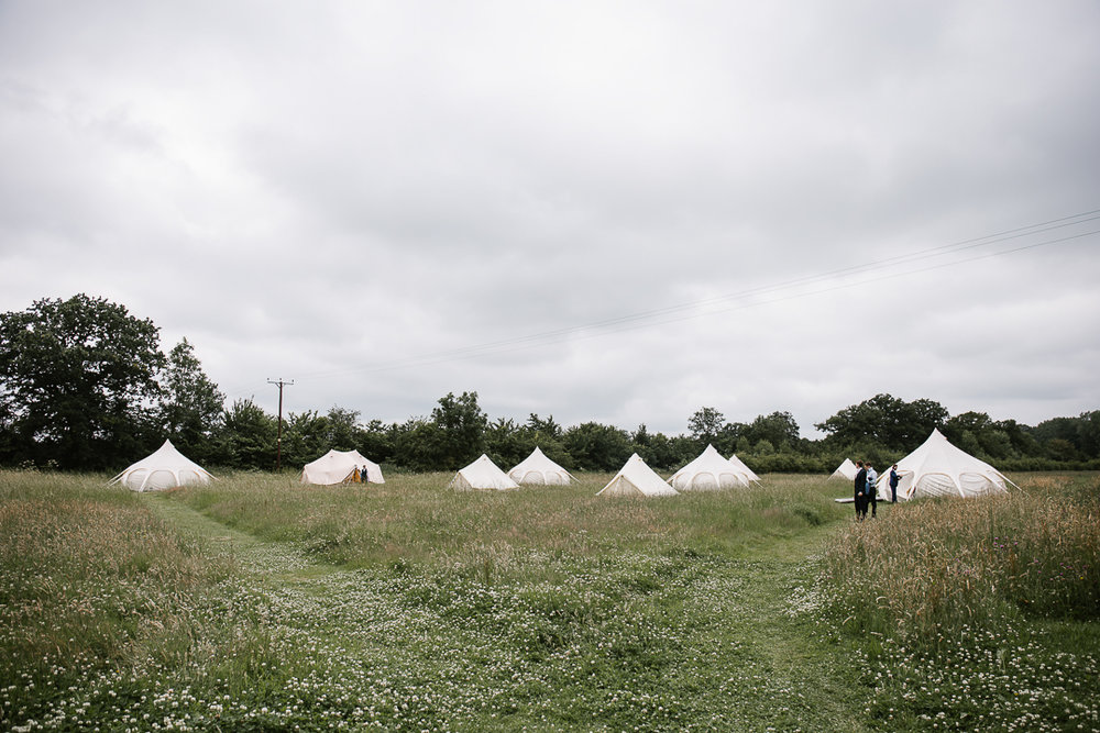 Field full of bell tents at a festival wedding at wildwood bluebell in the cotswolds