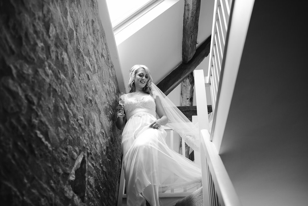 black and white photo of bride walking down the stairs before her wedding