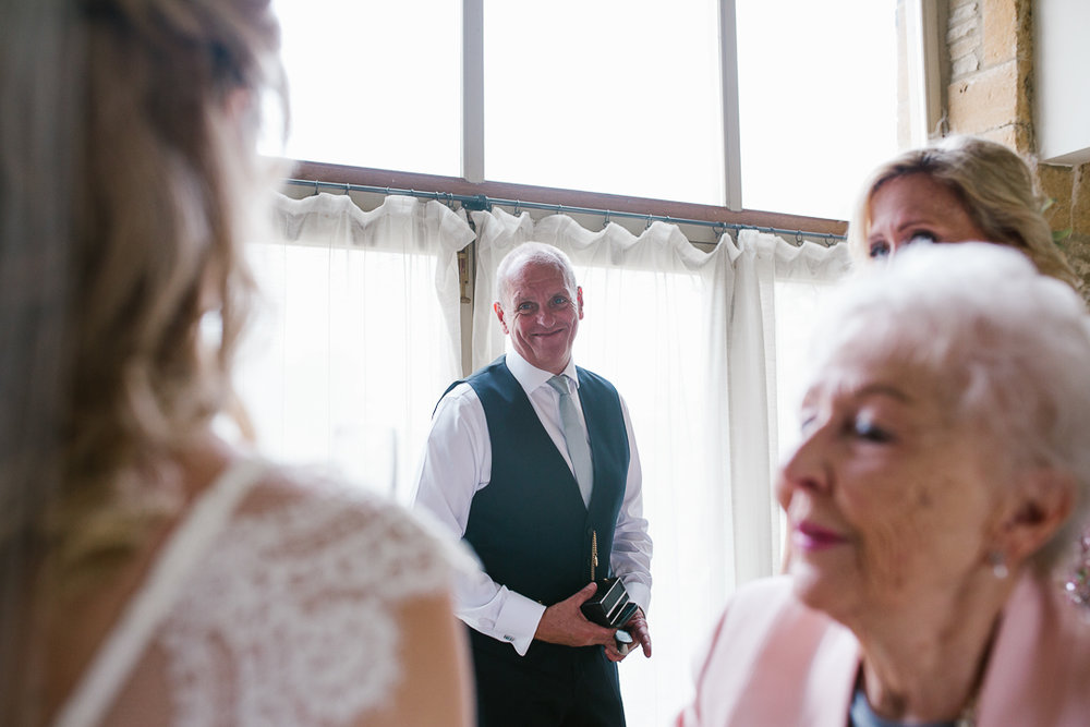 emotional and happy photo of father of the bride as he sees his daughter in her wedding dress for the first time