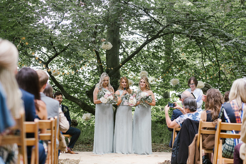 natural photo of bridesmaids doing an emotional reading during an outdoor wedding blessing