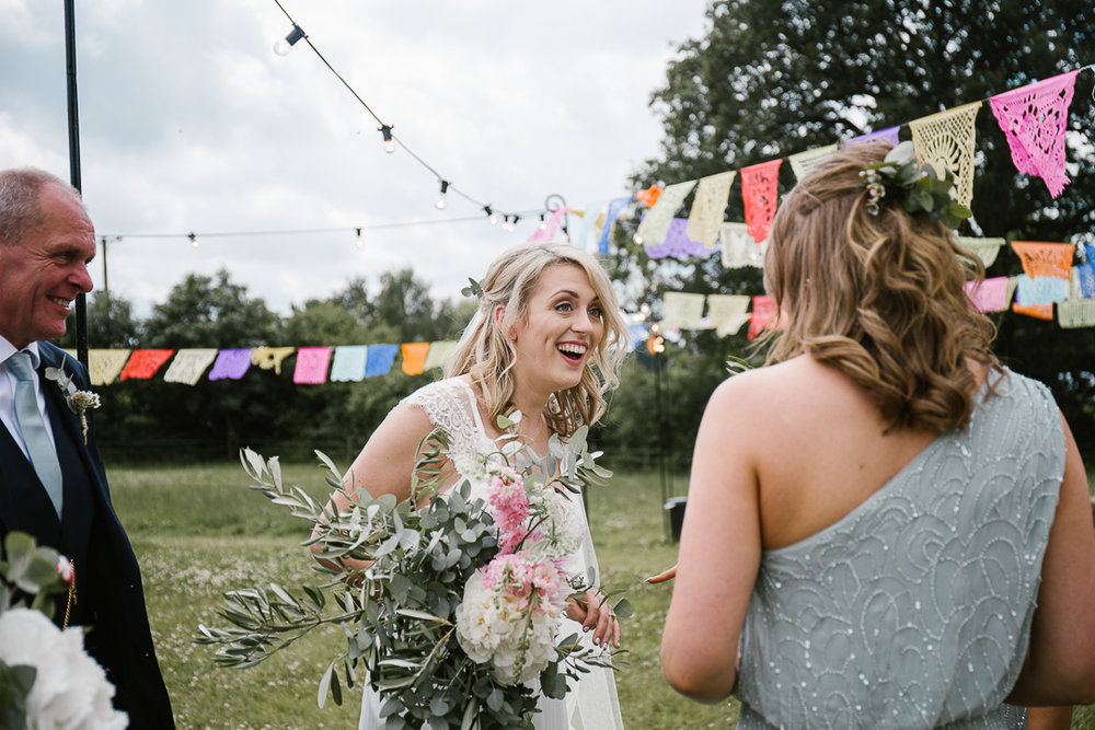 documentary wedding photo of bride laughing after her woodland wedding ceremony