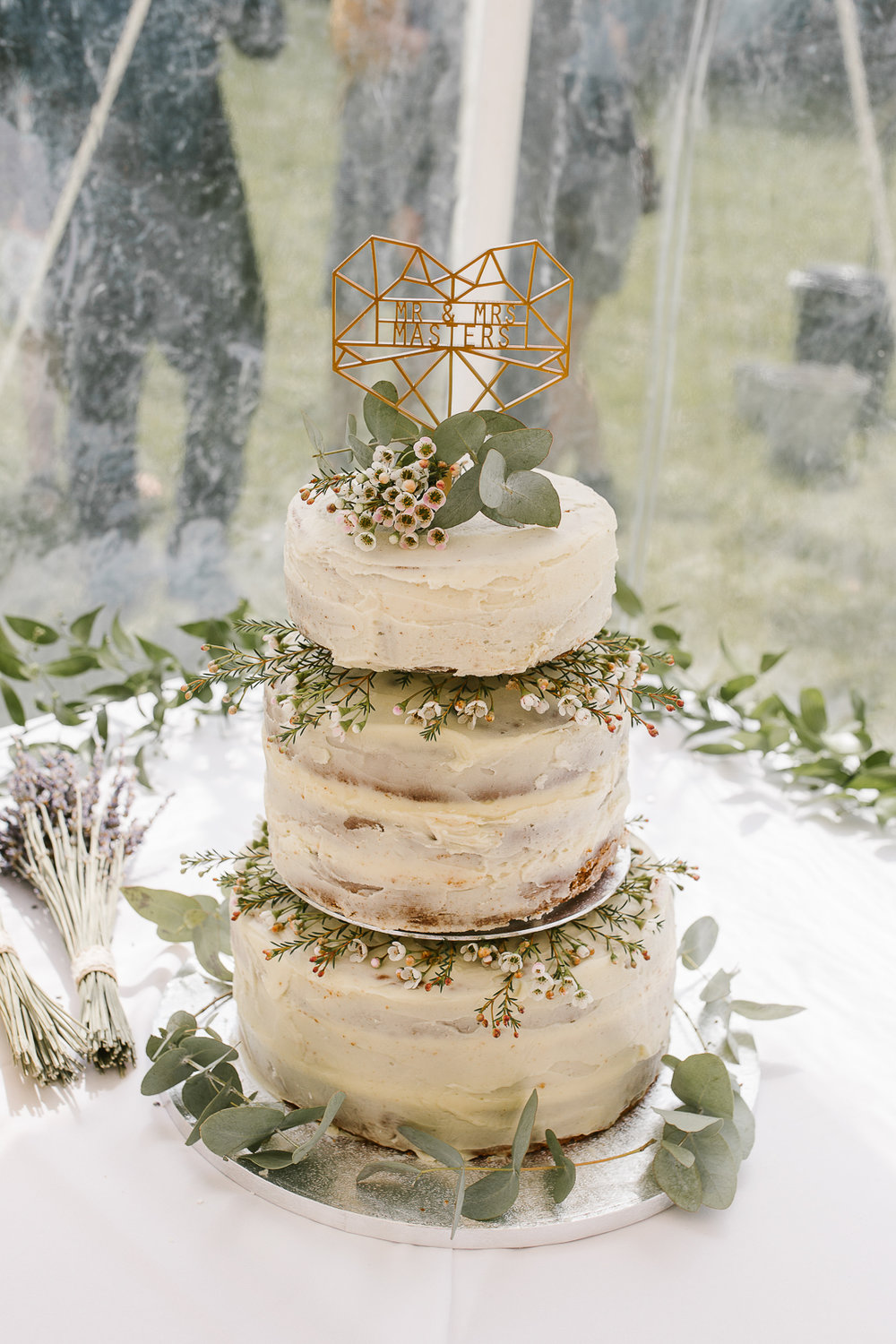 three tiered naked cake at marquee wedding in the cotswolds