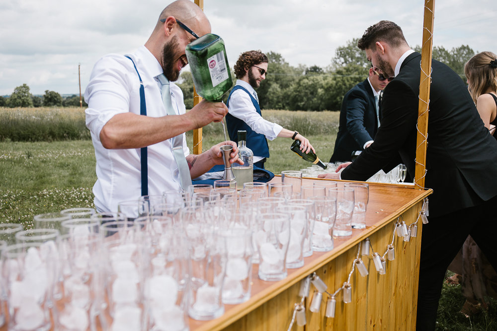 Groomsmen pouring gin into glasses on the DIY wooden bar