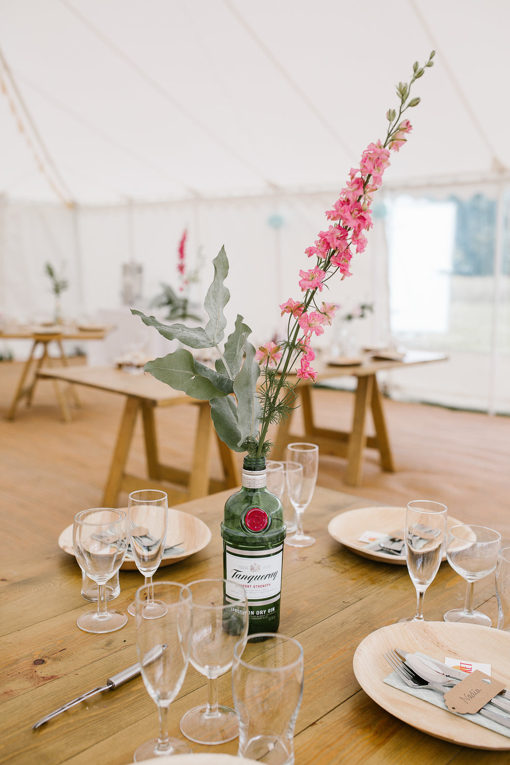gin bottle holding wild flowers as the table centrepiece at the DIY wedding in the Cotswolds