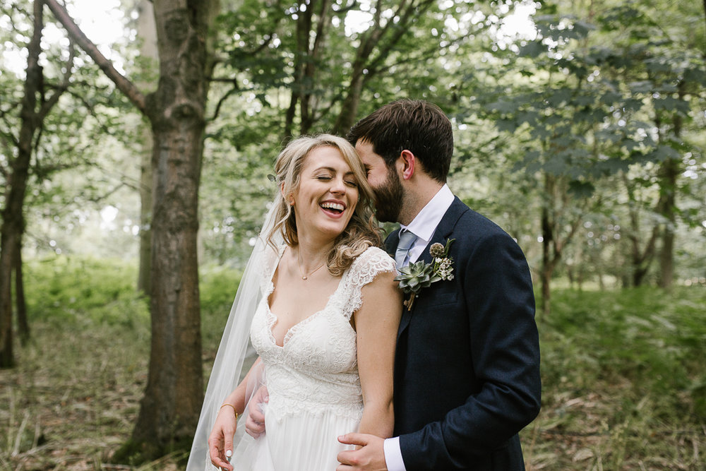 fun photo of bride and groom laughing together at their summer wedding