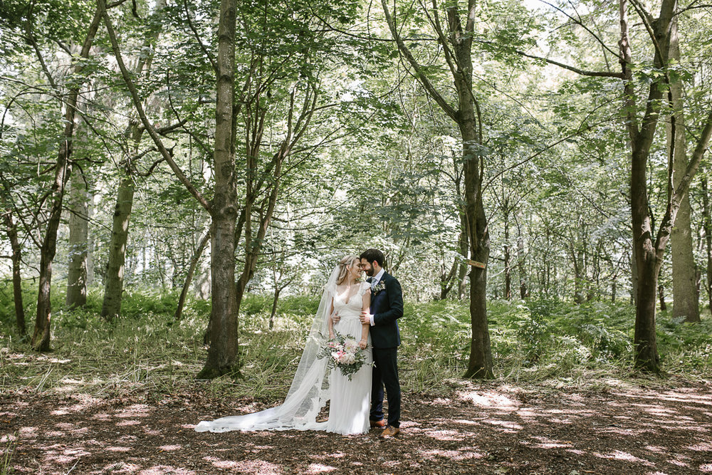 full length photo of bride and groom snuggled up in the forest after their forest wedding