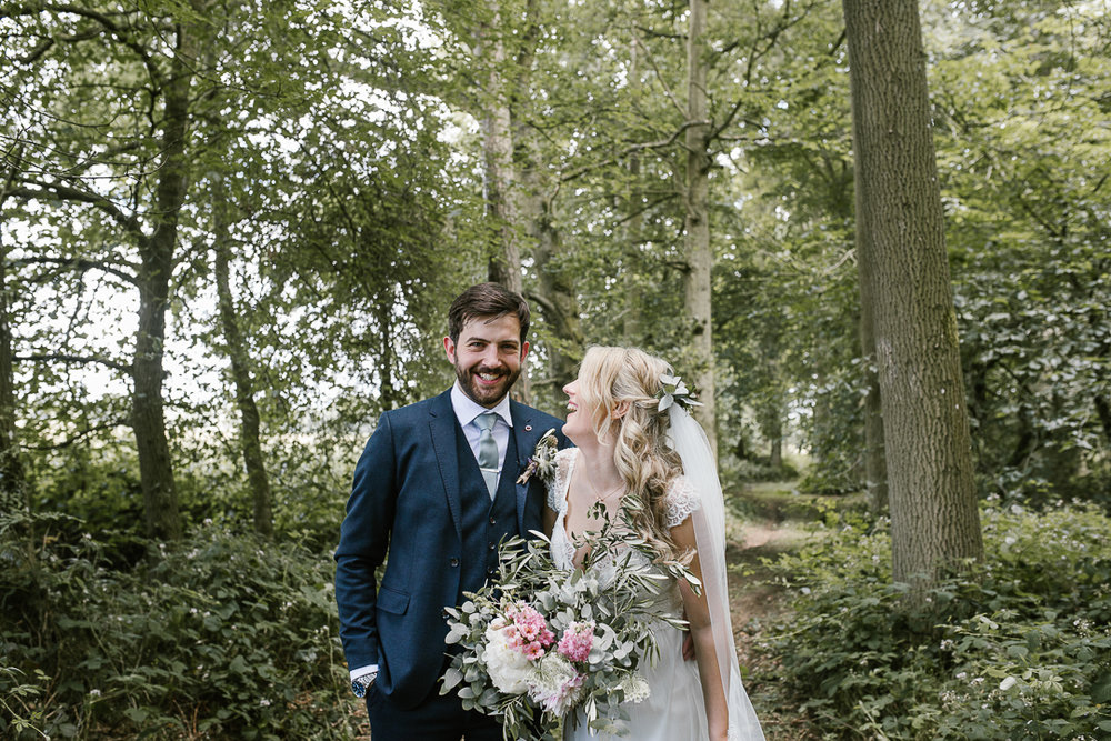happy photo of bride and groom in the woodlands  at their woodland wedding in the cotswolds