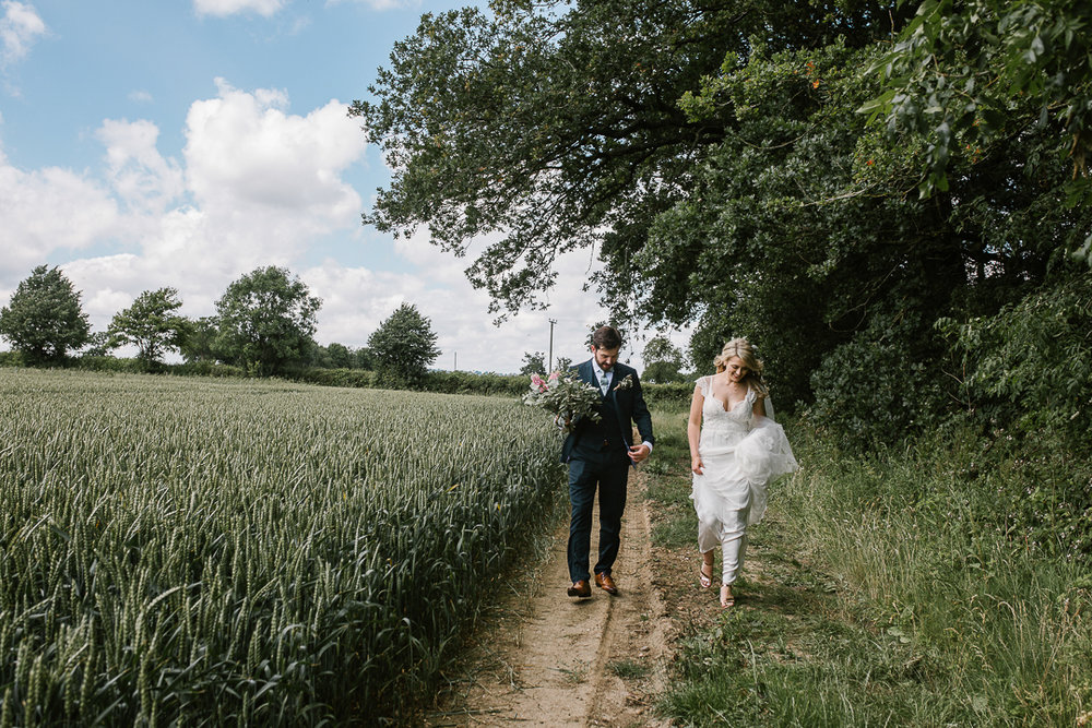 bride and groom walking through a crop field at their festival summer wedding