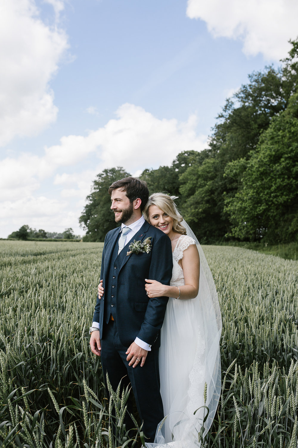 natural photo of bride and groom standing in a field at outdoor ceremony in the cotswolds