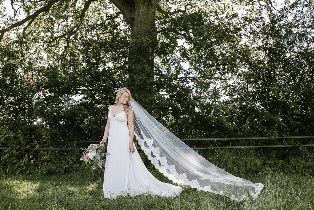 romantic photo of bride in Anna Campbell boho dress and long veil in the forest