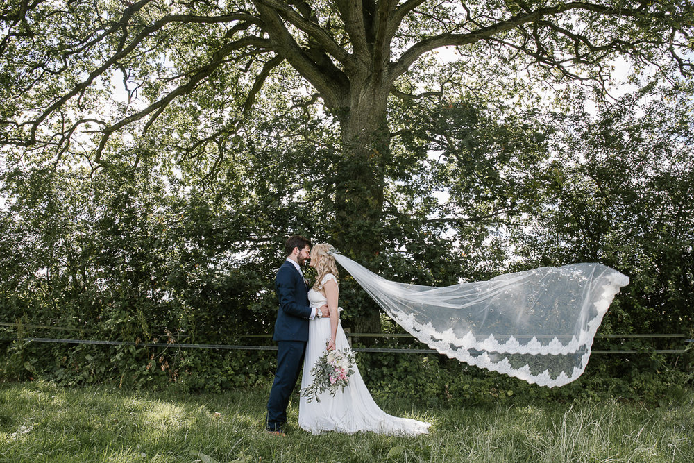 romantic photo of bride and groom kissing in a field with the brides long veil blowing through the air
