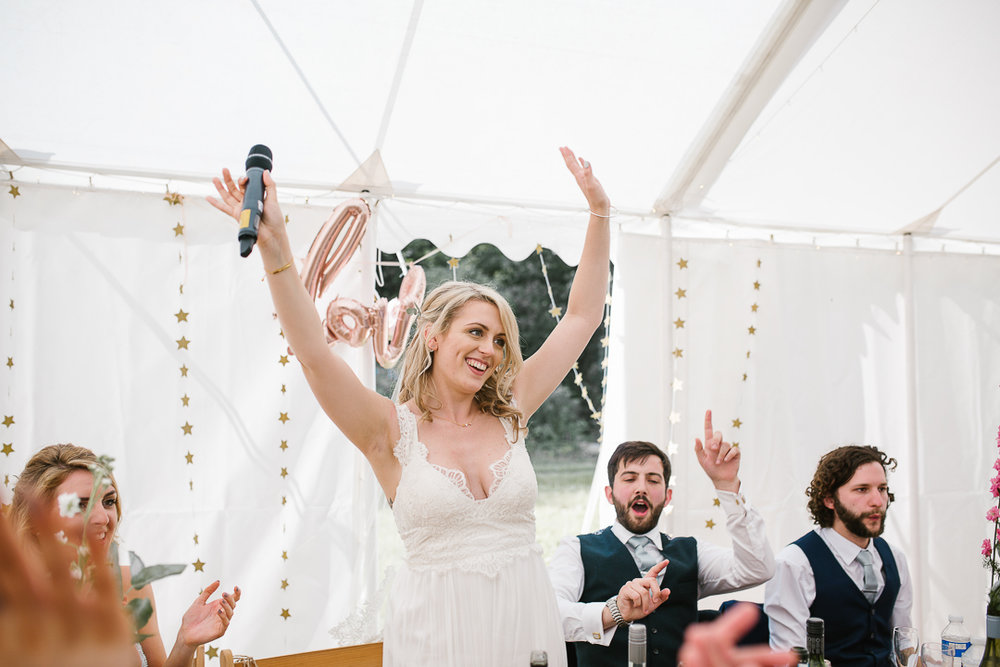 fun photo of bride celebrating doing a brides speech during her festival wedding