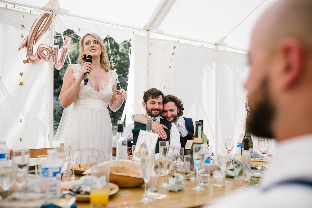 emotional photo of bride doing a bride speech while the groom cries with his best man