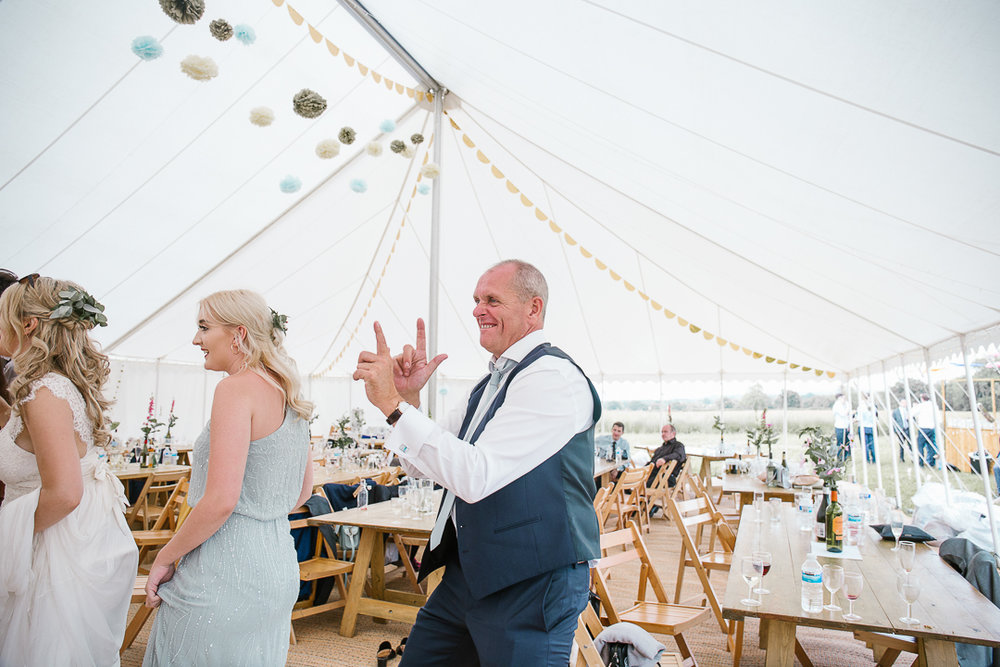 fun photo of father of the bride dancing on the marquee dancefloor at wedding in the cotswolds