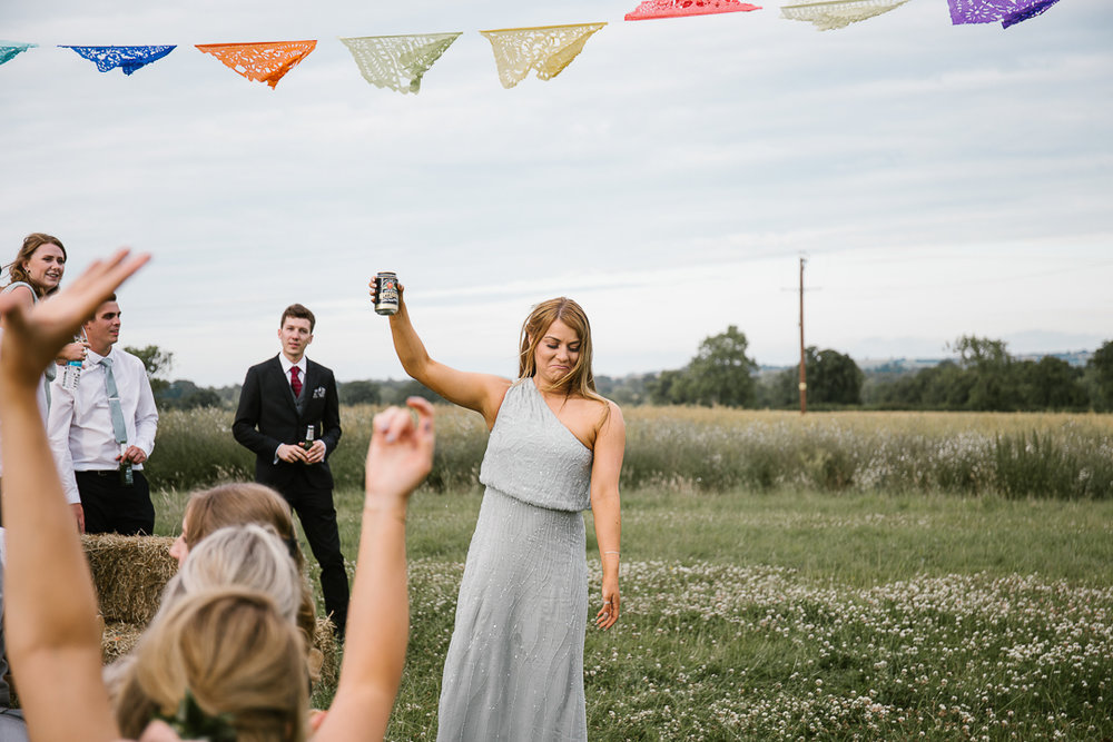 bridesmaid holding cider in hand cheering the wedding guests at the outdoor wedding