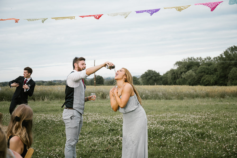 bridesmaid having cider poured down her face as she parties at festival wedding in the cotswolds