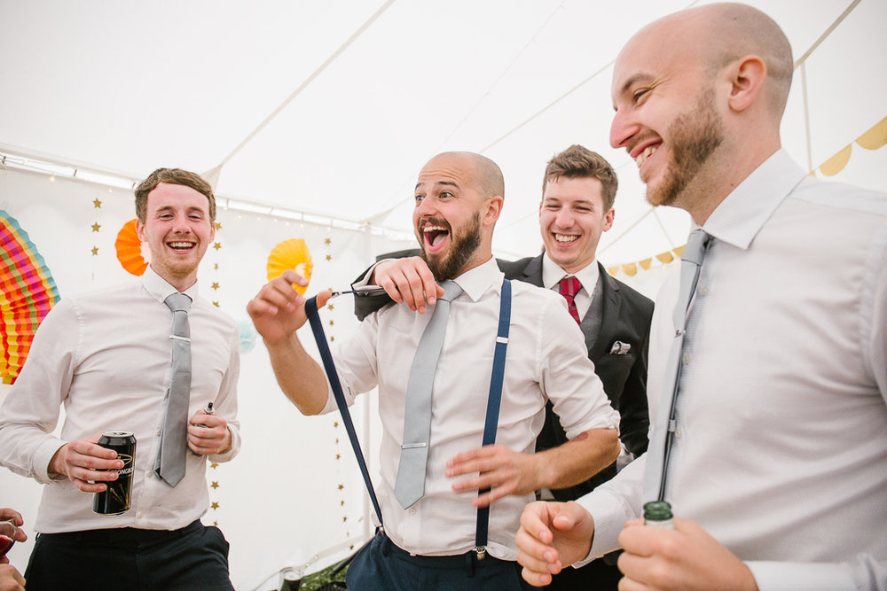 fun photo of groomsmen dancing at the festival themed wedding