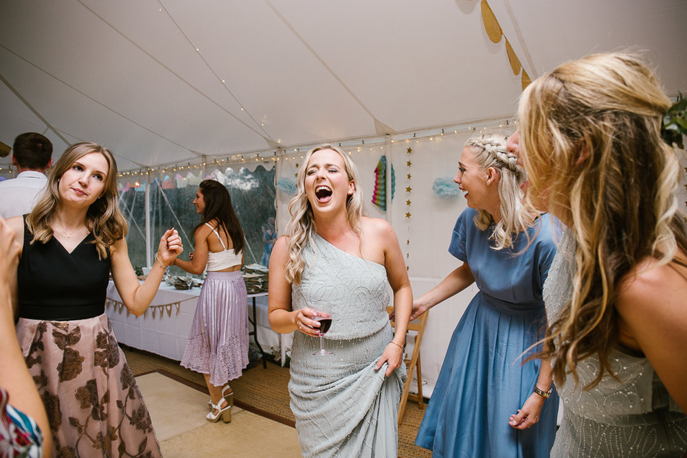 candid photo of bridesmaids laughing on the dance floor at the marquee wedding venue
