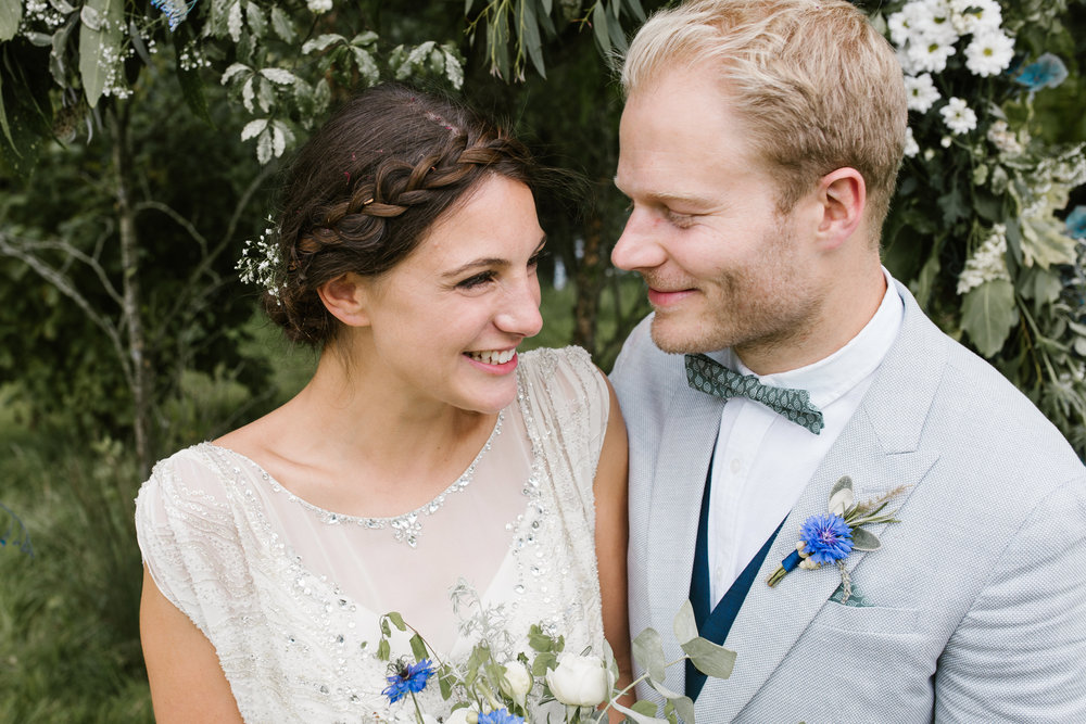 natural and relaxed photo of bride and groom smiling happily together after their outdoor back garden wedding ceremony at their festival wedding in somerset