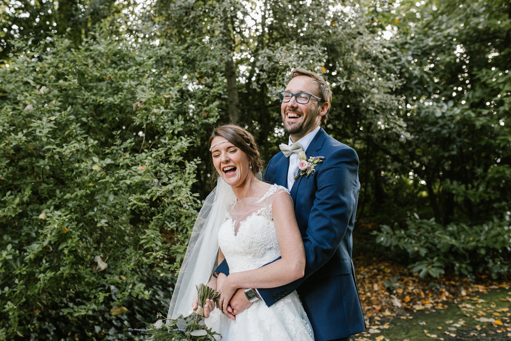 pendrell hall wedding- bride and groom hold onto one another laughing after their gin themed wedding- staffordshire wedding photography